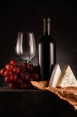 delicious red wine with grapes and cheese on black