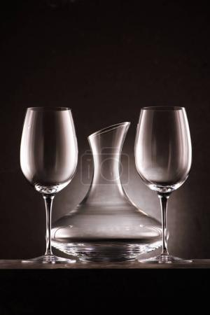 empty decanter between two wineglasses on black
