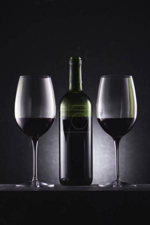 glasses filled with red wine and wine bottle in middle on black
