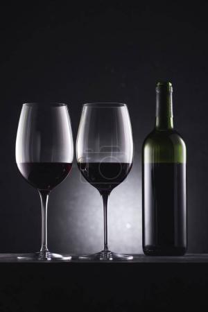 glasses filled with red wine and wine bottle on black
