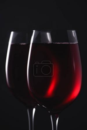 close-up shot of glasses full of luxury red wine on black