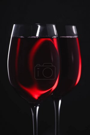 close-up shot of glasses full of red wine on black