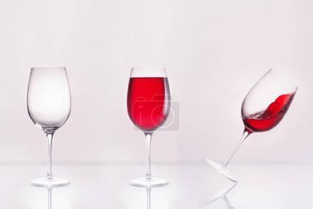 verre à vin vide avec plein et incliné en rangée sur la surface réfléchissante et sur blanc