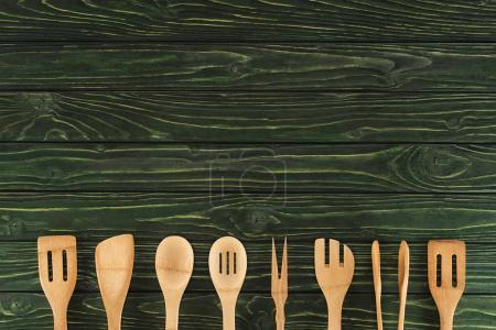 top view of kitchen utensils placed in row on rustic wooden table