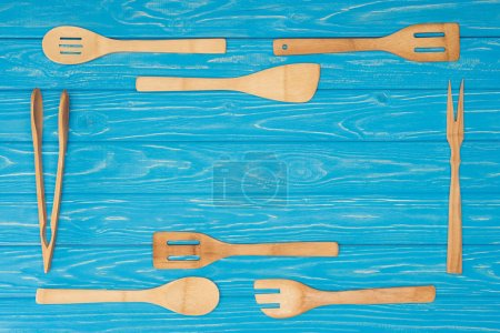top view of set of kitchen utensils on blue wooden table