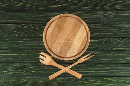 top view of round cutting board, spatula and fork for meat on wooden table
