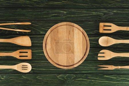 top view of round cutting board between kitchen utensils on wooden background
