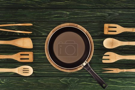 top view of frying pan on round cutting board between wooden kitchen utensils on table