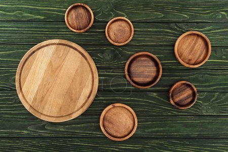 top view of different types of wooden round cutting boards on table