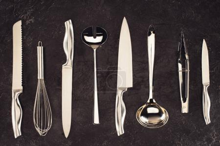 top view of kitchen utensils placed in row on black marble table