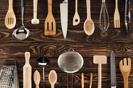 top view of different kitchen utensils placed in two rows on wooden table