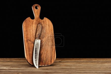 Photo for Closeup view of knife and wooden cutting board on black background - Royalty Free Image