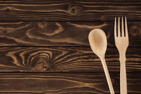 top view of fork and spoon on wooden table