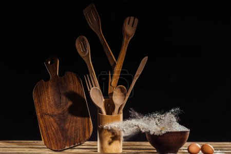 flying cutting board, kitchen utensils, flour from bowl and two eggs on table on black background