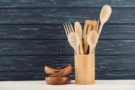 closeup view of ramekins and kitchen utensils in front of wooden wall