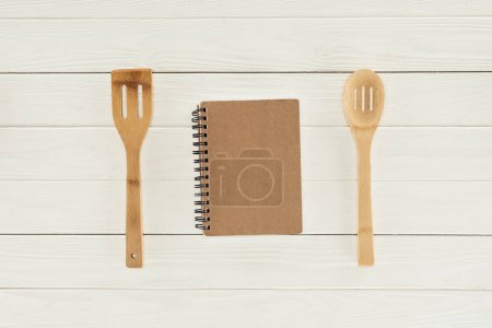 top view of textbook between two wooden spatulas on white table