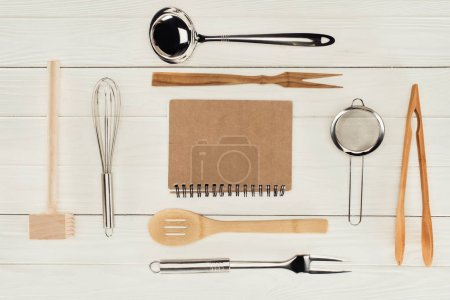 elevated view of textbook and kitchen utensils on wooden white table