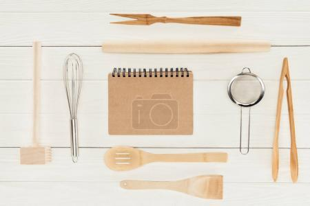 Photo for Top view of textbook and kitchen utensils on wooden white table - Royalty Free Image