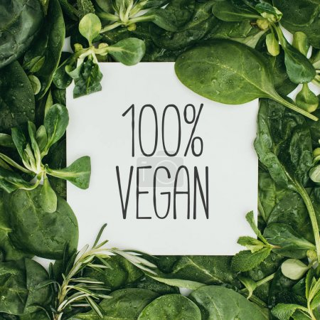 100 percent vegan inscription on white card and wet green leaves