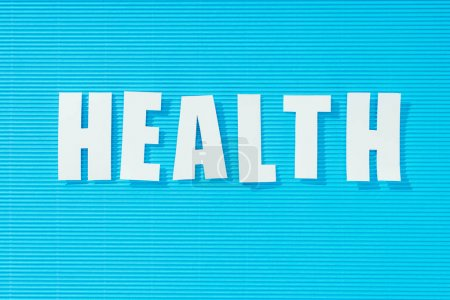 white word health on bright blue striped background, health concept