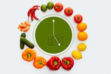 top view of circle of vegetables and fruits with green clock inside isolated on white