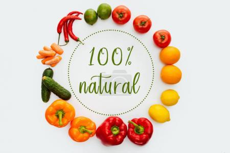 Top view of circle of vegetables and fruits with text 100% Natural isolated on white