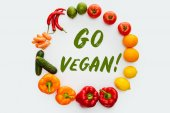 top view of circle of vegetables and fruits with text Go Vegan isolated on white