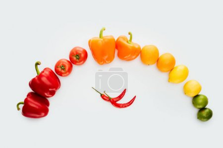 top view of curve of colored vegetables and fruits isolated on white