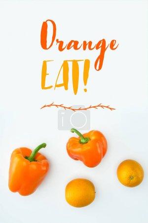 Photo pour Vue de dessus des poivrons orange et oranges avec texte Orange manger isolé sur blanc - image libre de droit