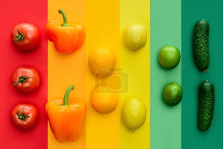 top view of ripe bell peppers, oranges and limes on colored surface
