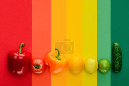 top view of ripe fruits and vegetables on colored surface