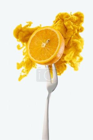 Photo pour La moitié d'orange sur la fourche et de l'encre jaune isolé sur blanc - image libre de droit