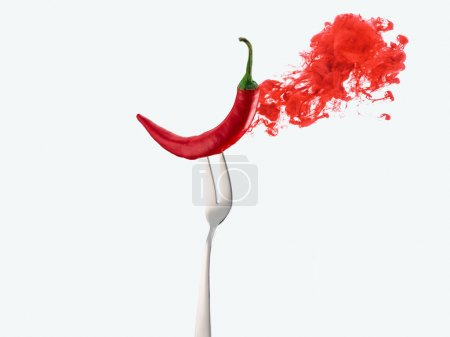 Photo for Red chili pepper on fork and red ink isolated on white - Royalty Free Image