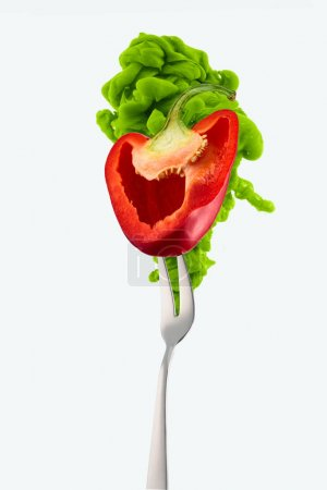 half of red bell pepper on fork and green ink isolated on white