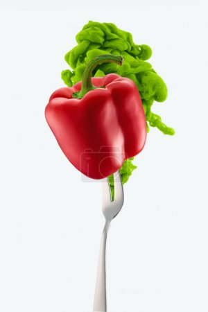 red bell pepper on fork and green ink isolated on white
