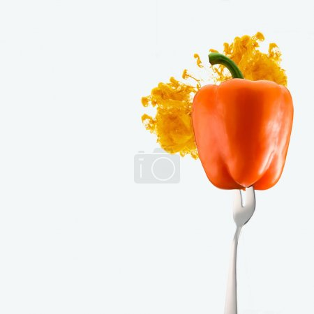 Photo pour Poivron orange sur la fourche et l'encre orange isolé sur blanc - image libre de droit