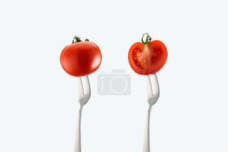 cut and whole tomatoes on forks isolated on white