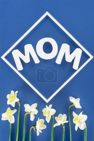 top view of daffodils and word mom in frame isolated on blue, mothers day concept