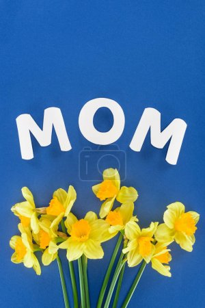 top view of yellow daffodils and word mom isolated on blue, mothers day concept