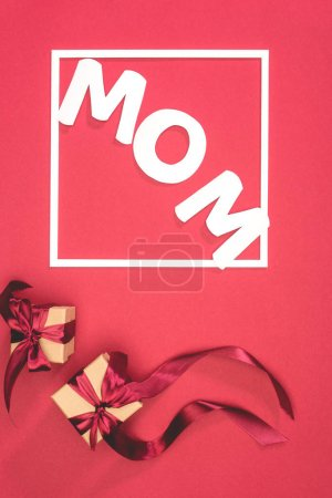 Photo for Top view of gift boxes and word mom in frame on red surface, mothers day concept - Royalty Free Image