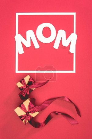 top view of gift boxes with ribbons and word mom in frame on red surface, mothers day concept