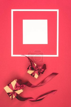 top view of gift boxes with ribbons and frame with cube on red surface