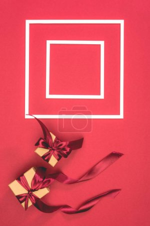 top view of gift boxes and frames on red surface