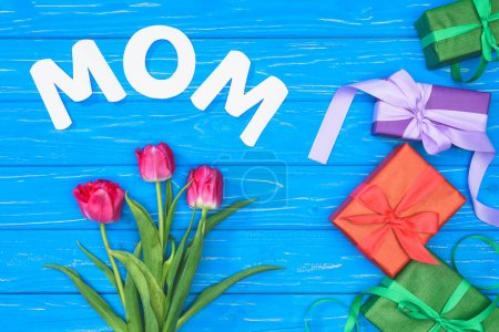 top view of gift boxes, pink tulips and word mom on blue table, mothers day concept