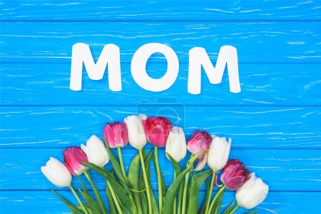 elevated view of bouquet of pink and white tulips and word mom on blue table, mothers day concept