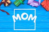 top view of gift boxes and word mom in frame on blue table, mothers day concept
