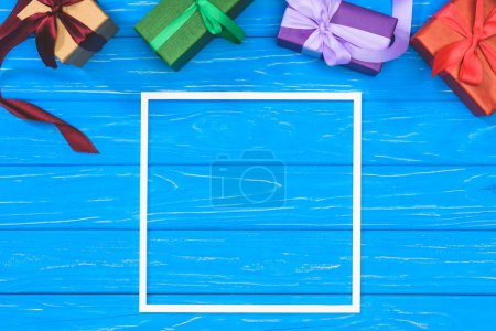 Photo for Top view of gift boxes and blank frame on blue table - Royalty Free Image
