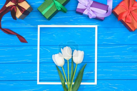 top view of gift boxes and white tulips in frame on blue table