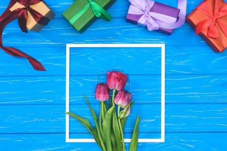 top view of gift boxes and pink tulips in frame on blue table