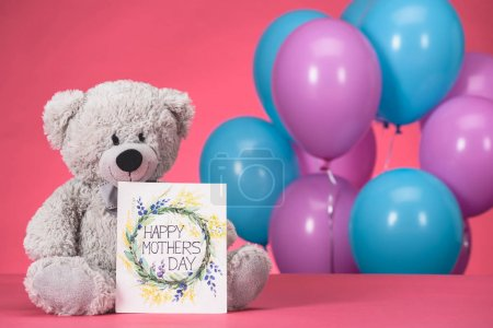 teddy bear and postcard with text Happy Mothers Day on pink tabletop